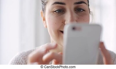 happy woman with smartphone at home