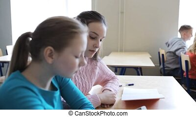 students with smartphone on lesson at school - education,...
