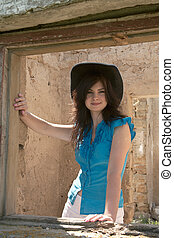 Cowgirl on a background of ruins of an old farm