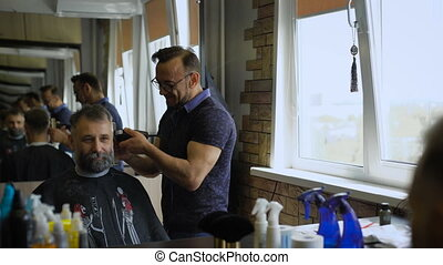 Stylish Barber works with the haircut Client aged with gray...