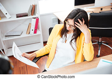 Businesswoman analysing graphics on paper in office