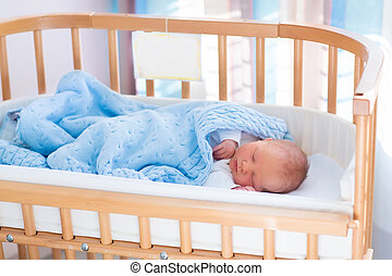 Newborn baby boy in hospital cot - Newborn baby in hospital...
