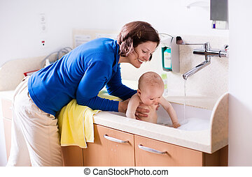 Mother bathing baby in hospital room