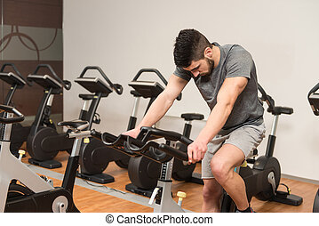 Muscular Man Doing Cycling In Modern Fitness Center