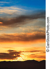 Sun behind dark mountain silhouettes, with colorful sky and...