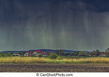 Cloudburst over village - Cloudburst over a village and...