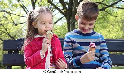 Children licking an ice cream cone on a sunny spring day in...