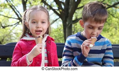 Happy children eating ice cream - Two happy children eating...