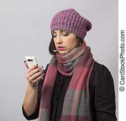 Woman wearing an shirt and hat with scarf using a mobile...