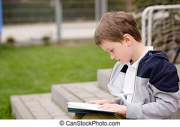 7 year old boy reading a book on the terrace