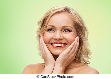 smiling woman with bare shoulders touching face - beauty,...