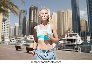 woman running or jogging over dubai city street - fitness,...