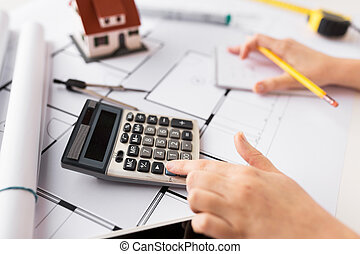 close up of architect hand counting on calculator -...