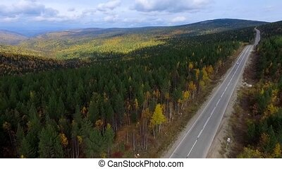 A birds-eye aerial flight over the road autumn forest Russia...