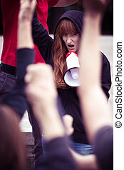 Young female rebel shouting into a megaphone