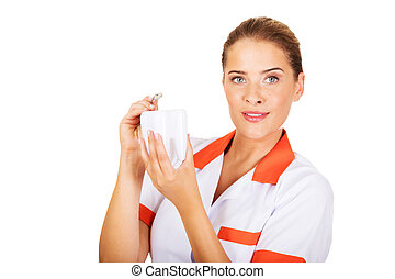 Young female dentist holding a tooth model and dental mirror...