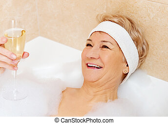 Senior woman relaxing in bath with glass of champagne.