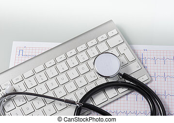 stethoscope, ecg and keyboard on doctors desk