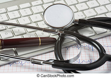stethoscope, fountain pen and keyboard on doctors desk
