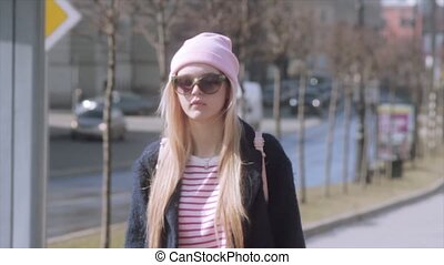 Beautiful young girl is walking on a beautiful sunny streets. Slow motion