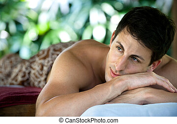Man At Spa - An attractive caucasian man lying down on a...