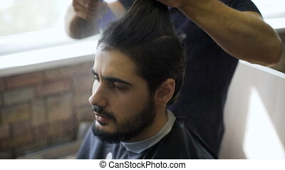 Getting groomed. Shot of a handsome bearded barber giving a...