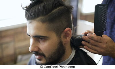 Getting groomed. Shot of a handsome bearded barber giving a haircut to his client using trimmer