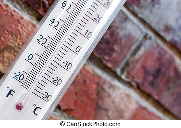 Thermometor measuring hot summer weather with a brick wall...