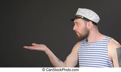 Side view of bearded captain sends air kiss - Side view of...