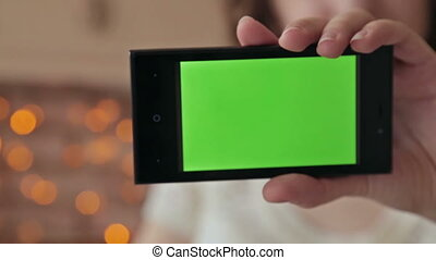 Smartphone green screen. Young woman showing smart phone...