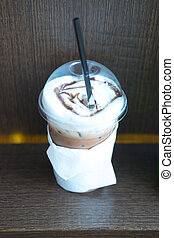 take-home cup of ice coffee on wooden table