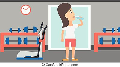 Woman drinking water - A sportive woman drinking water in...