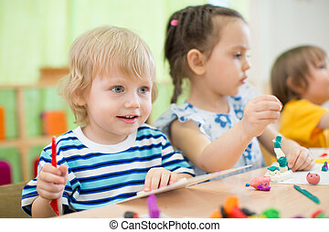 kids making arts and crafts in day care centre together -...