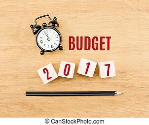 Budget 2017 year on wood cube with pencil and clock top view...