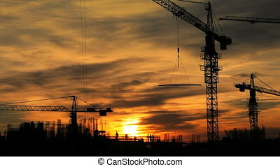 Construction Site - Construction cranes fading from sunset...