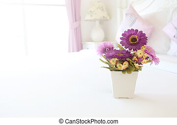Vintage pink artificial flowers on a table in the white...