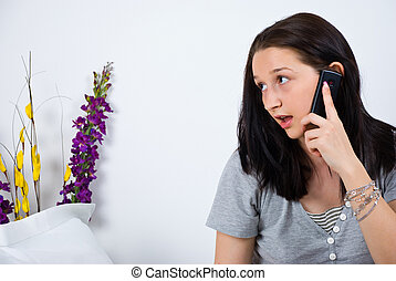 Woman talking at ceel phone in bed