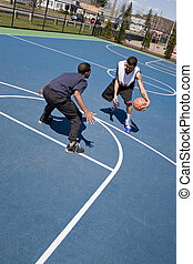 Guys Playing Basketball - A young basketball player guards...