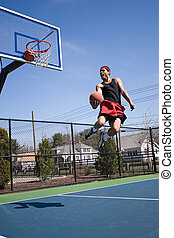 Skilled Basketball Player - A young athlete flying through...