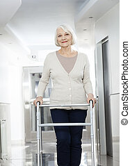 Senior Woman Using Walker At Rehab Center - Portrait of...