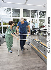 Nurse In Scrubs Assisting Man With Walker At Fitness Studio
