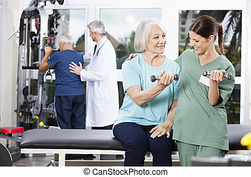 Nurse Guiding Senior Woman Exercising With Dumbbell -...
