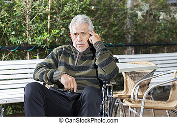 Pensive Senior Male Patient Sitting In Wheelchair At Lawn -...