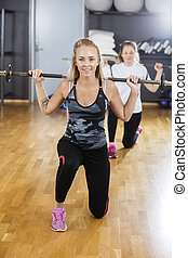 Woman Kneeling While Lifting Barbell In Gym - Smiling young...