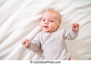 Little baby boy lying on bed in onesie, white bedroom - Cute...