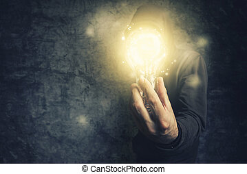 Hooded unidentifiable person holding light bulb as symbol of...
