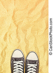 Feet in sneakers standing on war desert sand - Sneakers on...
