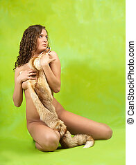 Naked  girl covered with fox fur over green