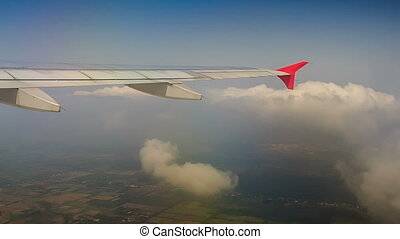 Airliner Wing Cuts White Clouds While Ascending - airliner...