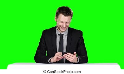 Businessman sitting at the table and uses phone Green screen...